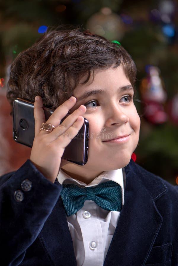 Il giovane ragazzo sveglio sta parlando sullo smartphone2 fotografia stock