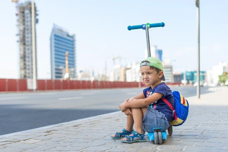 Il giovane ragazzo sveglio sta sedendosi sul motorino di scossa ad una fermata dell'autobus vicino al centro commerciale degli em fotografia stock