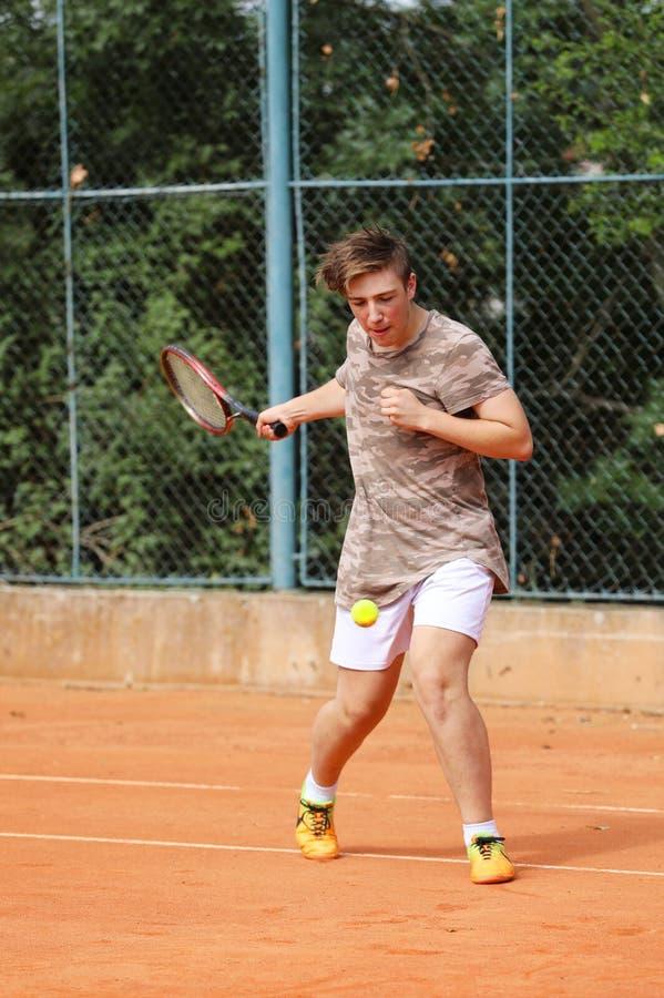 Il giovane ragazzo teenager gioca a tennis sull'estate immagine stock