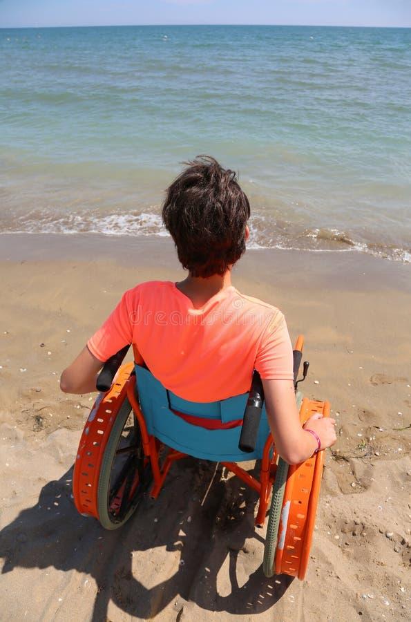 Il giovane ragazzo utilizza la sedia a rotelle speciale davanti al mare fotografie stock