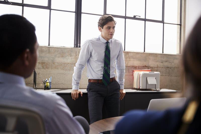 Il giovane responsabile maschio sta ascoltante ad una riunione, fine su fotografie stock libere da diritti