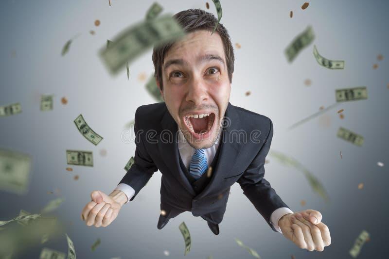 Il giovane riuscito uomo d'affari è un vincitore I soldi stanno cadendo da sopra fotografie stock libere da diritti