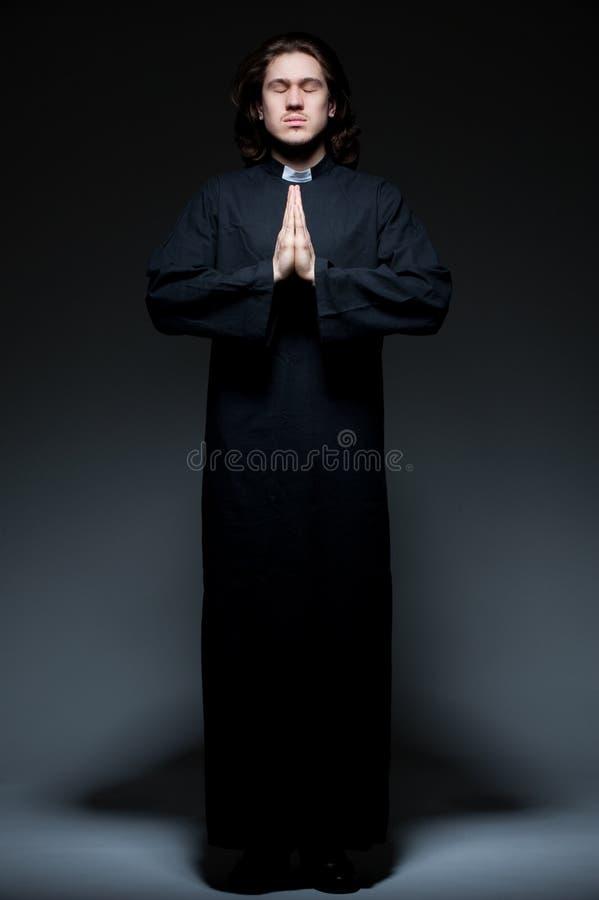 Il giovane sacerdote sta pregando contro priorità bassa scura immagine stock