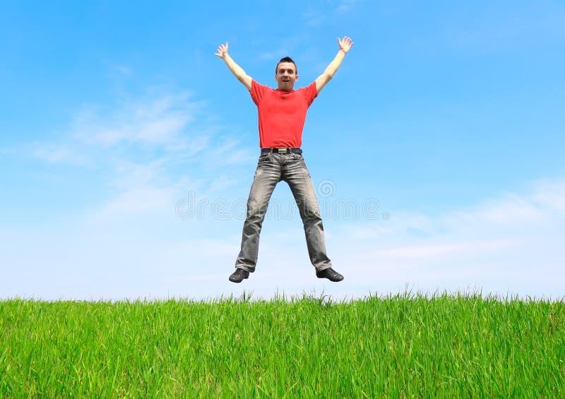 Il giovane salta sul prato fotografie stock libere da diritti
