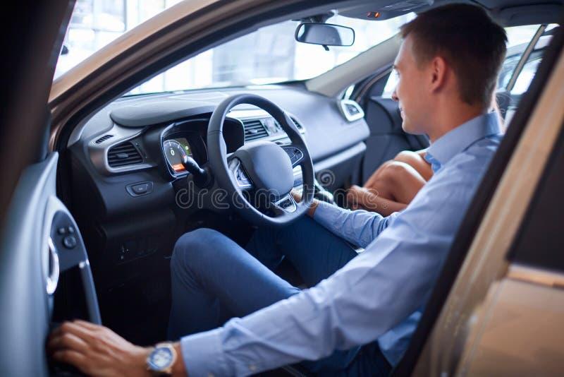 Il giovane sceglie una nuova automobile Il concetto di acquisto dell'automobile nuova immagini stock
