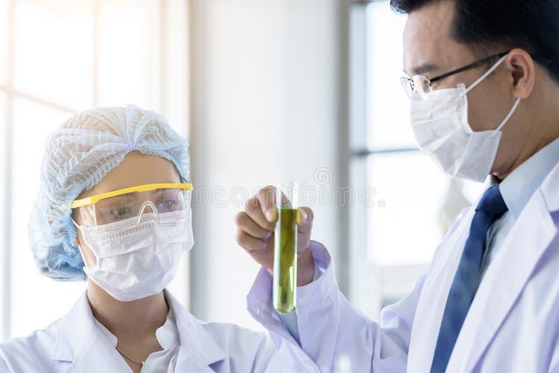 Il giovane scienziato asiatico dello studente che ricerca e che impara con lo scienziato senior ha insegnamento in un laboratorio fotografia stock