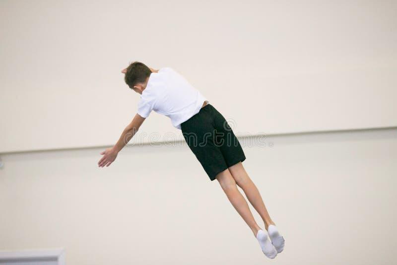 Il giovane si esercita relativi alla ginnastica nella palestra immagini stock libere da diritti