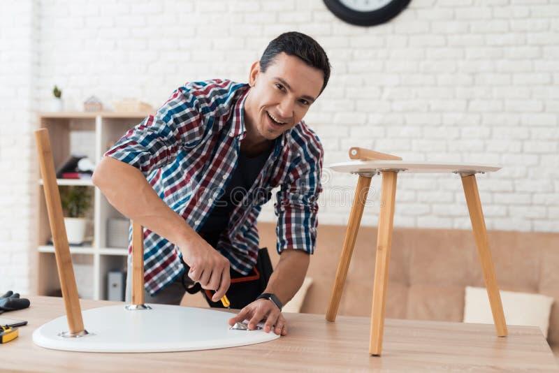 Il giovane si prova per piegare il suoi tavolino da salotto e panchetti fotografia stock libera da diritti
