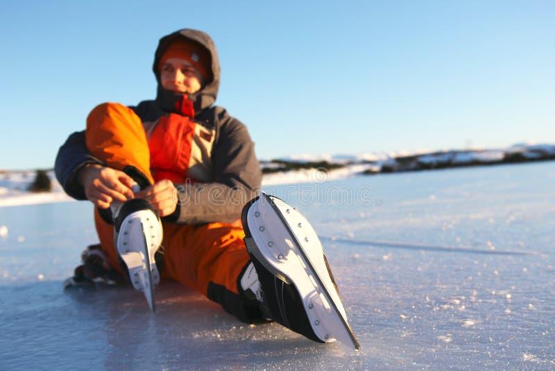 Il giovane si siede sul ghiaccio che stringe i laccetti sui suoi pattini da ghiaccio immagini stock