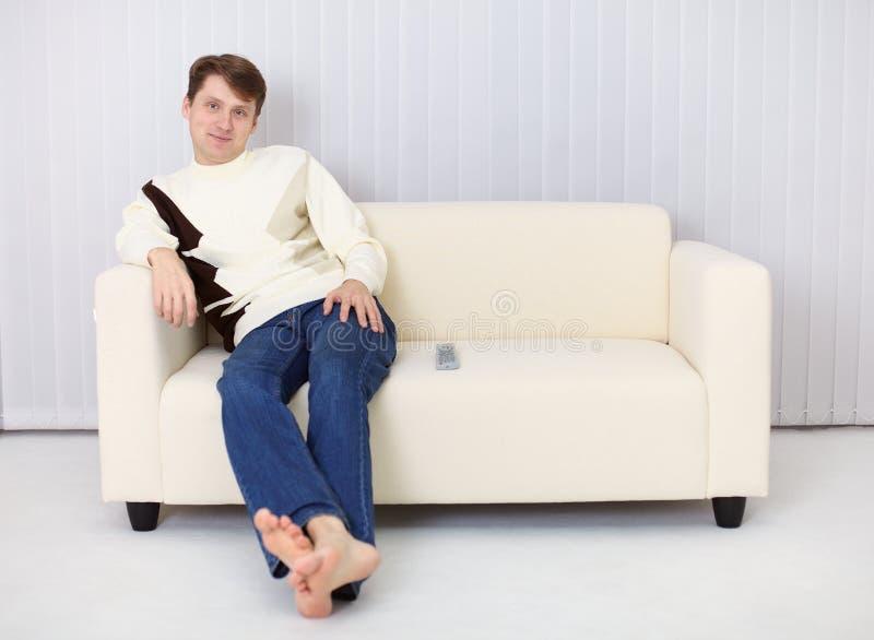 Il giovane si siede sul sofà ed ha resto fotografie stock