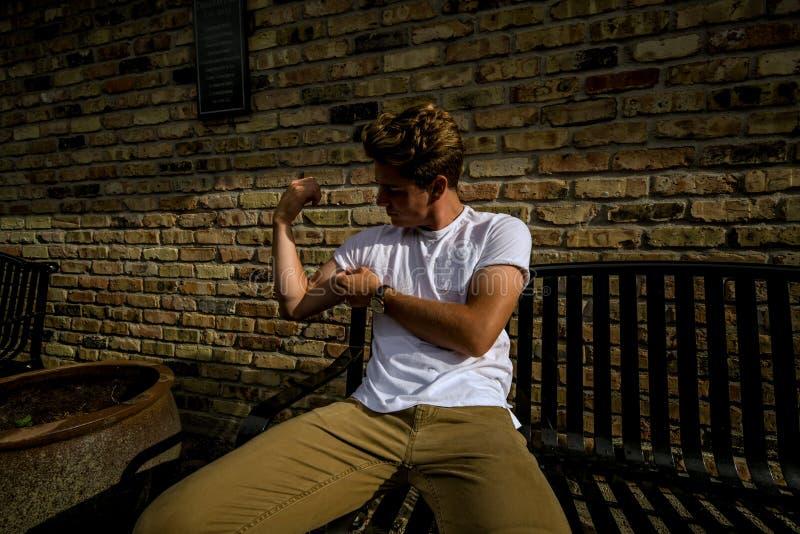 Il giovane si siede sulla flessione del banco della città fotografie stock libere da diritti
