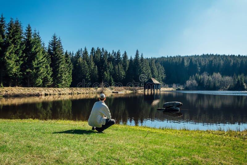 Il giovane si siede sullo stagno pulito piacevole con l'albero di legno della molla e della costruzione con cielo blu fotografia stock libera da diritti