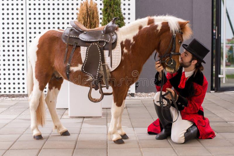 Il giovane signore con il cilindro ed il suo cavallino mostrano il loro sci preparato immagine stock libera da diritti