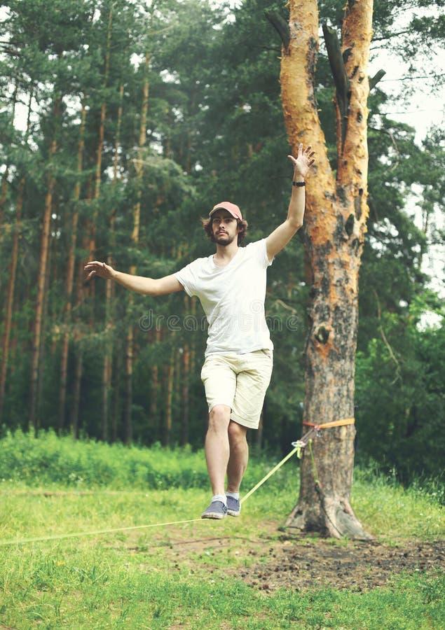 il giovane slacklining la camminata e l'equilibratura su una corda, slackline all'aperto fotografie stock