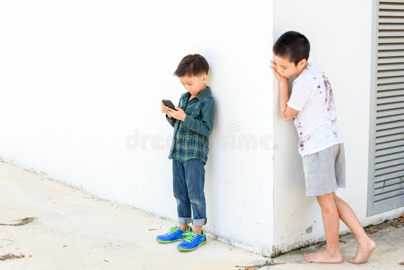 Il giovane smartphone del gioco del ragazzo paragona al ragazzo povero fotografie stock libere da diritti