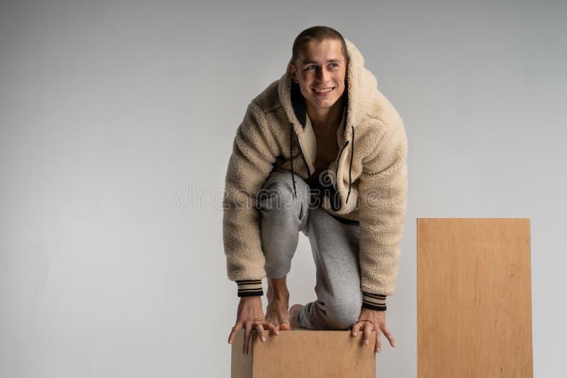 Il giovane sorridente astuto in sportwear si è accovacciato sul cubo di legno e sulla posa fotografia stock libera da diritti