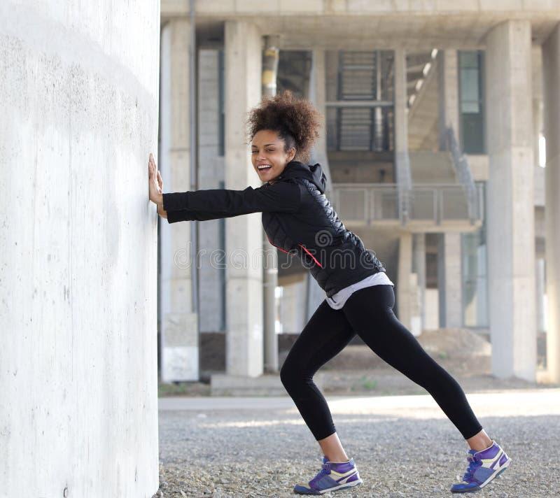 Il giovane sorridente mette in mostra la donna che allunga l'esercizio all'aperto fotografia stock