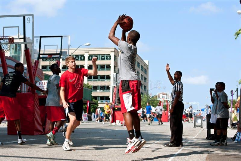 Il giovane spara il tiro in sospensione nel torneo di pallacanestro della via fotografia stock libera da diritti