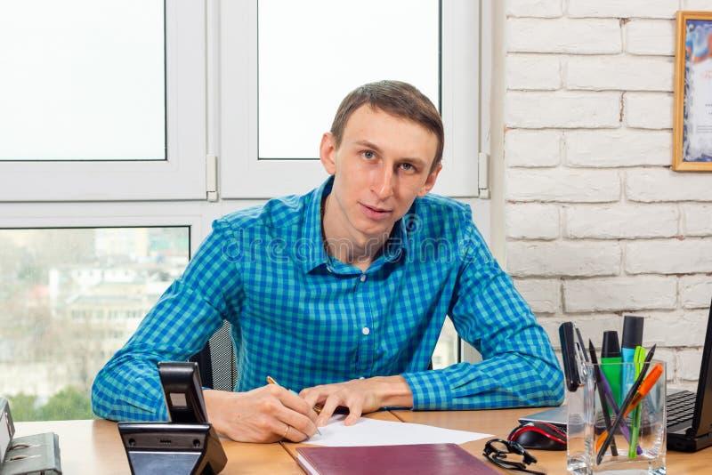 Il giovane specialista dell'ufficio alla tavola firma il documento fotografia stock libera da diritti