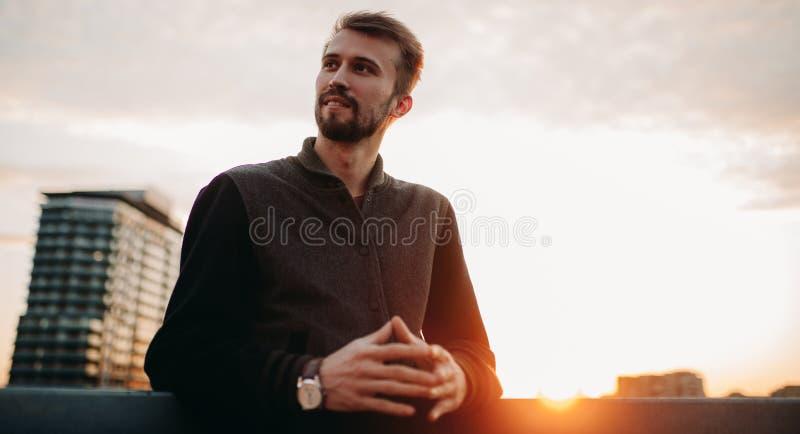 Il giovane sta e sorride sul tetto della casa contro fondo dei grattacieli e del tramonto immagini stock libere da diritti