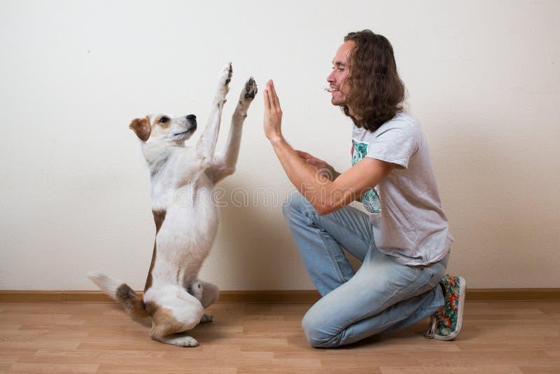 Il giovane sta giocando con il suo cane a casa fotografia stock