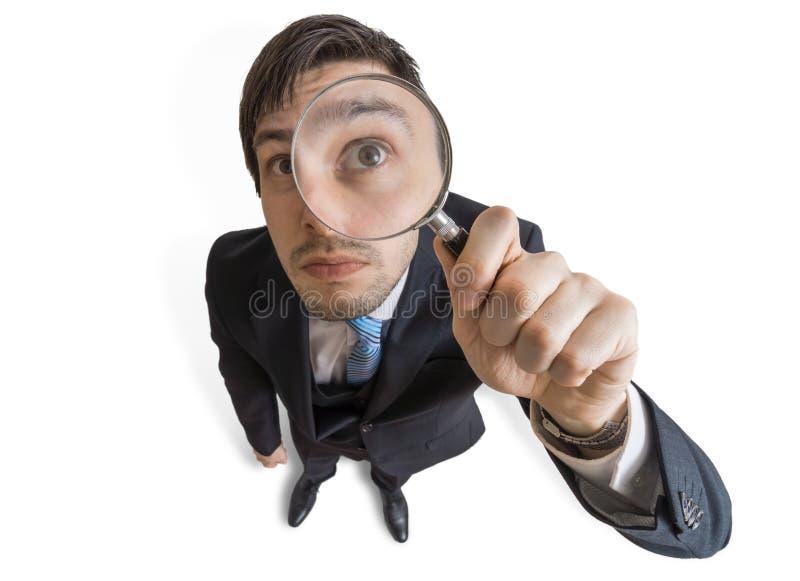 Il giovane sta guardando tramite la lente d'ingrandimento Isolato su priorità bassa bianca Vista da sopra immagine stock