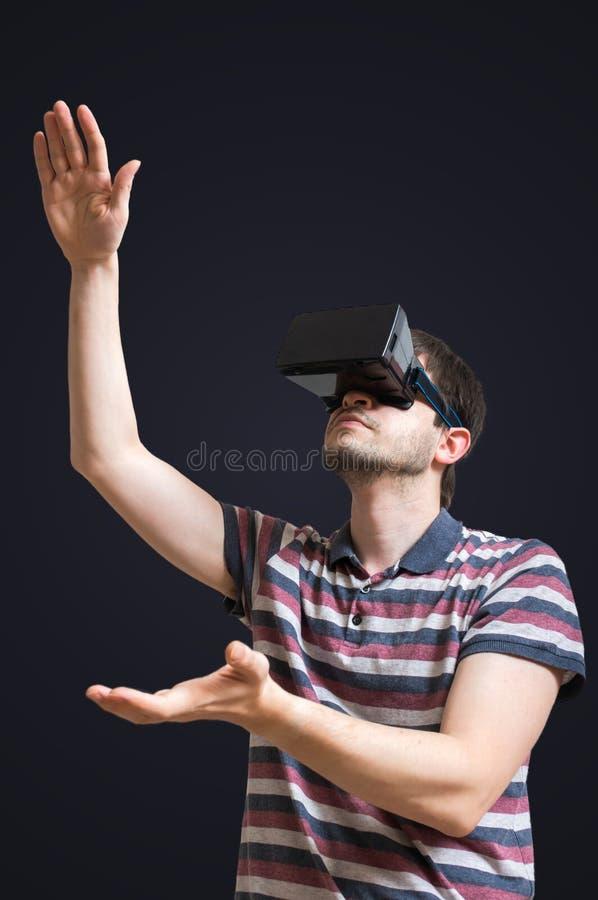 Il giovane sta indossando i vetri di realtà virtuale 3D Isolato sul nero fotografie stock libere da diritti