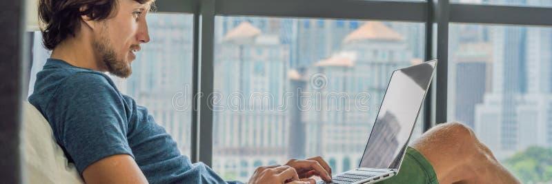 Il giovane sta lavorando ad un computer portatile nel suo letto su un fondo di una finestra panoramica che trascura i grattacieli fotografia stock libera da diritti
