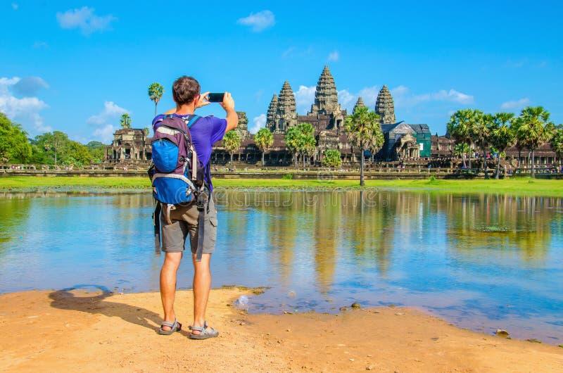 Il giovane sta prendendo una foto del tempio di Angkor Wat fotografia stock