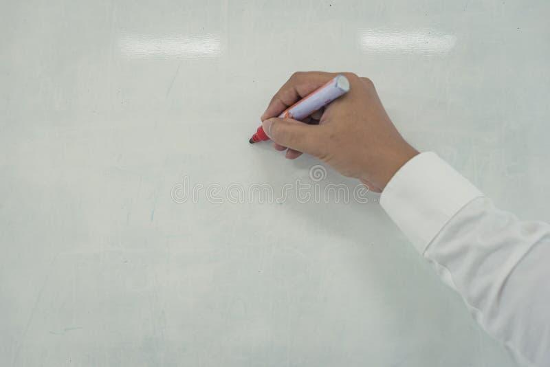 Il giovane sta scrivendo sulla lavagna fotografie stock libere da diritti