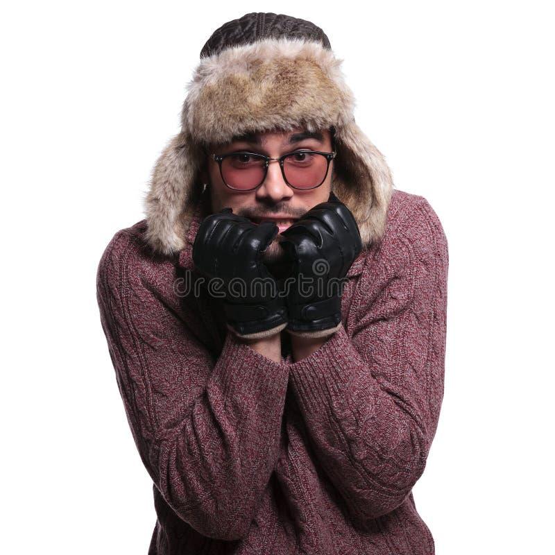Il giovane sta spaventando circa il freddo dell'inverno immagine stock