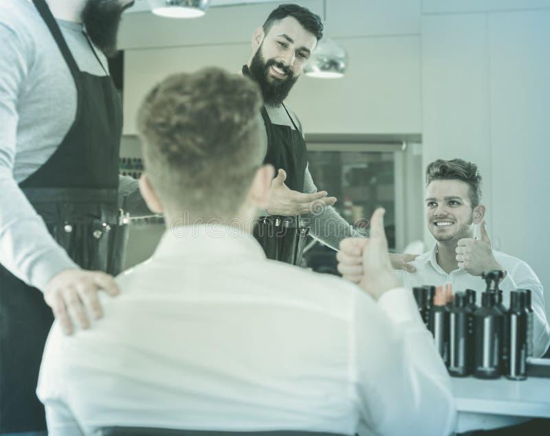 Il giovane stilista del tipo che dimostra il taglio di capelli finale al soddisfatto a clien fotografie stock libere da diritti