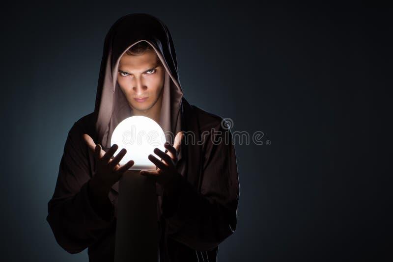 Il giovane stregone con sfera di cristallo nella stanza scura immagini stock libere da diritti