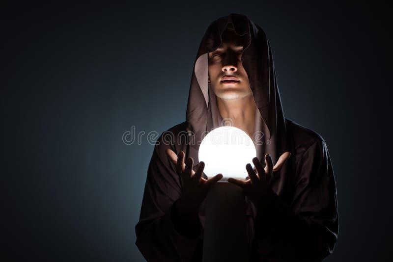 Il giovane stregone con sfera di cristallo nella stanza scura fotografia stock