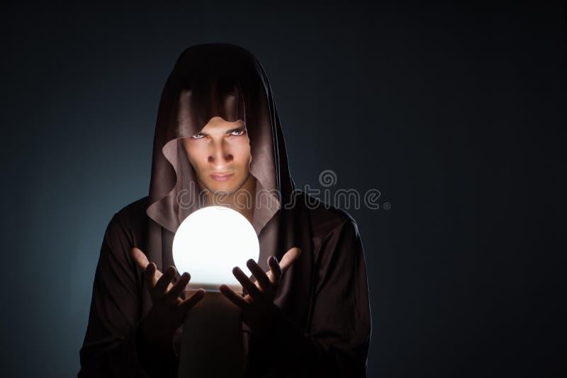 Il giovane stregone con sfera di cristallo nella stanza scura fotografia stock libera da diritti