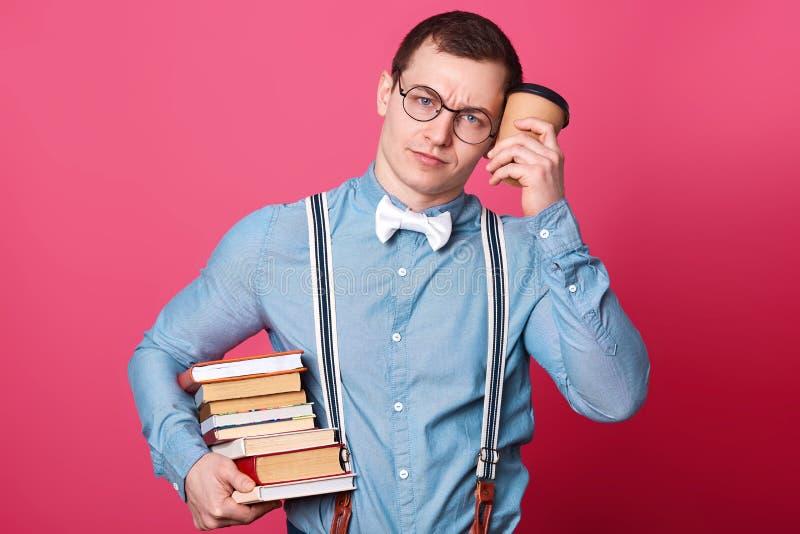 Il giovane studente in camicia blu in un tono, sembra sonnolento e exuasted, tiene il caffè vicino alla testa ed alla pila enorme immagini stock