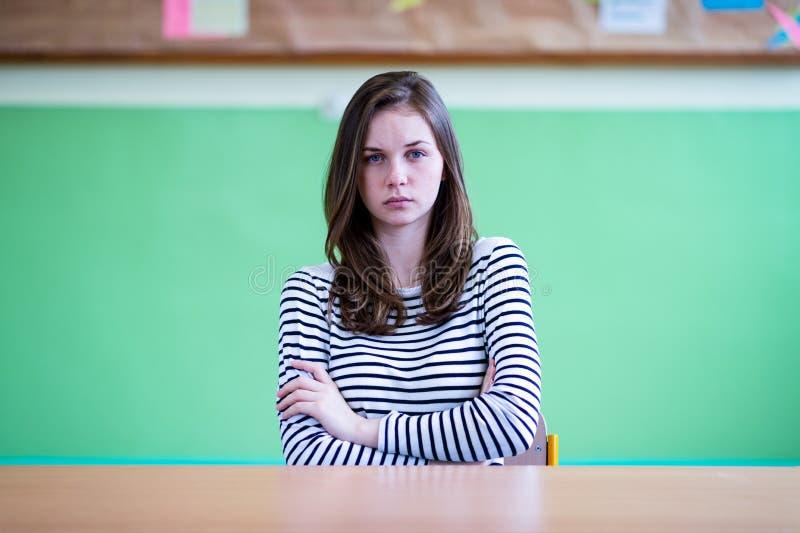 Il giovane studente femminile depresso ed ansioso della High School che si siede al suo scrittorio in un'aula, con le sue armi ha fotografia stock libera da diritti