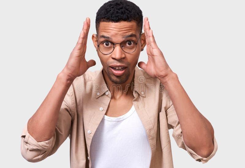 Il giovane stupito di afro bello sembra attrezzatura casuale surpried e d'uso, isolata sopra il fondo bianco dello studio fotografia stock libera da diritti
