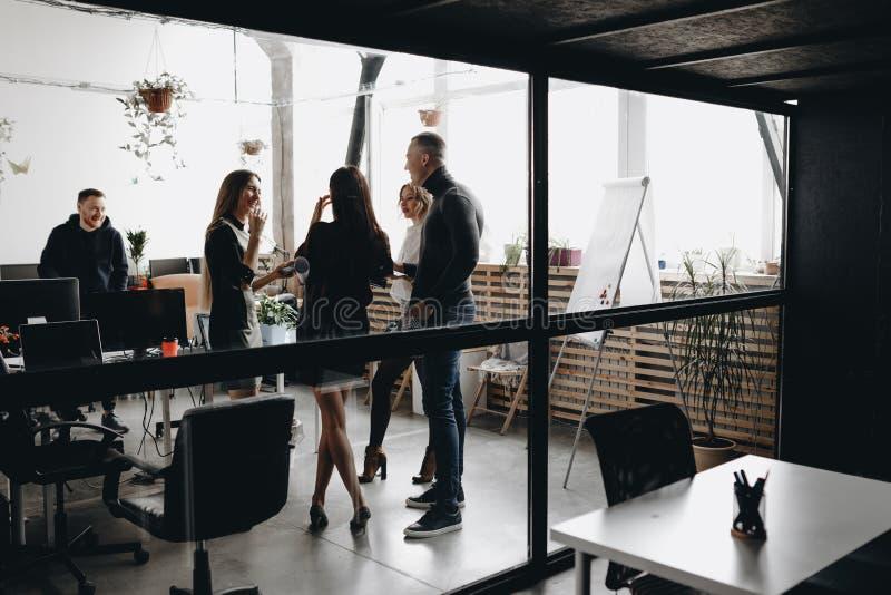 Il giovane supporto del gruppo insieme e parla dietro la parete di vetro nell'ufficio moderno leggero spazioso fornito di moderno fotografia stock