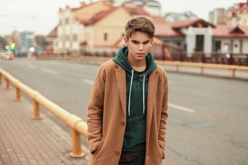 Il giovane tipo alla moda in un cappotto d'avanguardia con una maglia con cappuccio cammina fotografia stock libera da diritti