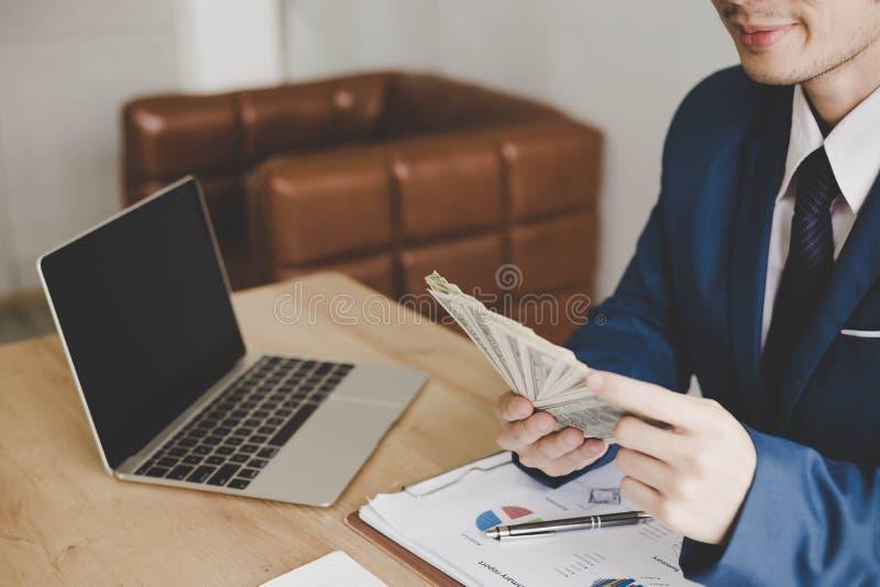 Il giovane tipo bello affascinante sta contando i soldi Handso attraente fotografia stock libera da diritti