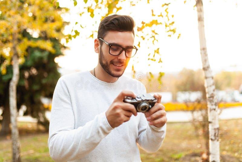 Il giovane tipo bello dei pantaloni a vita bassa cammina in un bello parco di autunno sui precedenti immagini stock libere da diritti