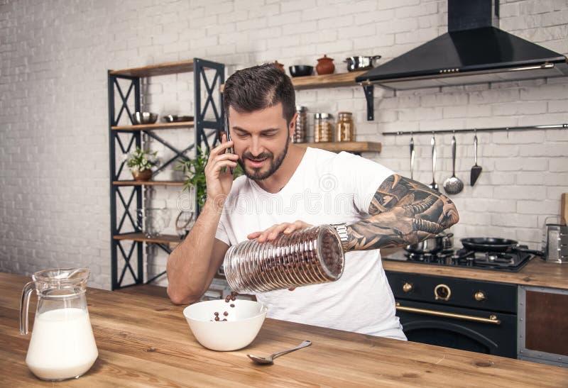 Il giovane tipo sorridente bello felice sta preparando la sua prima colazione al cereale mescolantesi della cucina con latte e st fotografie stock libere da diritti