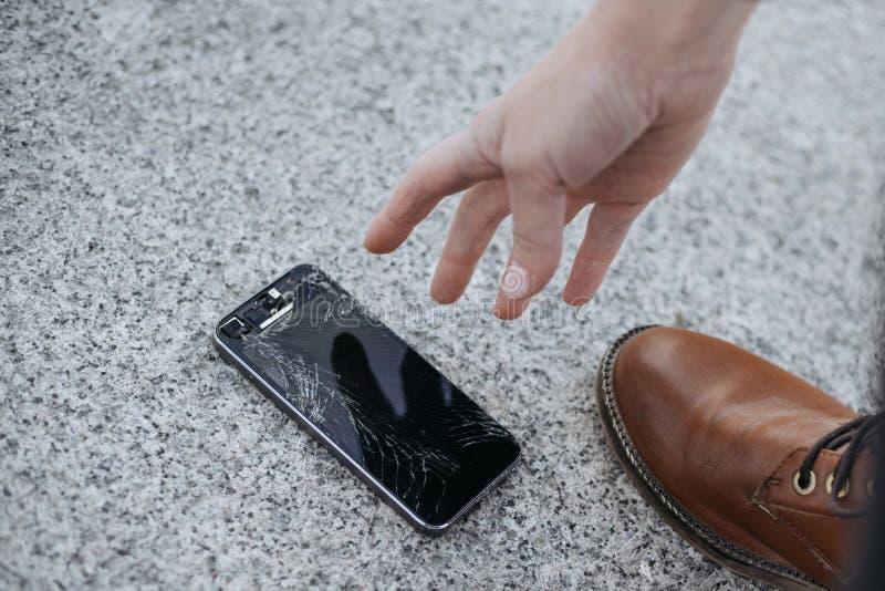 Il giovane turbato si siede e tiene uno smartphone rotto con uno schermo di vetro incrinato immagine stock libera da diritti