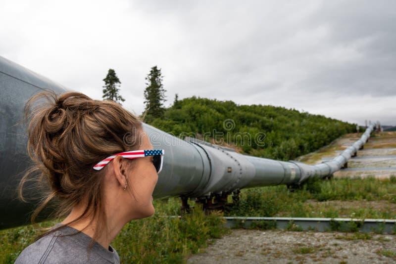 Il giovane turista della femmina adulta ammira la conduttura d'Alasca del trasporto immagini stock libere da diritti