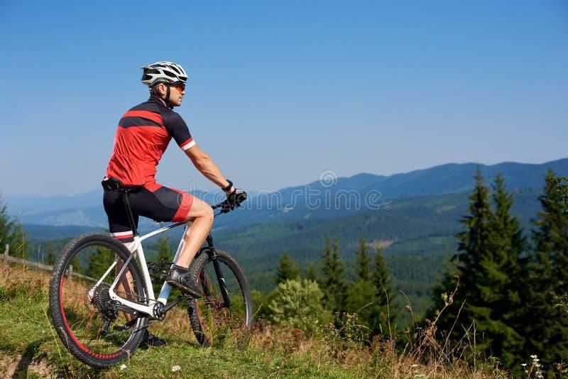 Il giovane turista professionale atletico ha smesso sopra la collina di godere di bella vista delle montagne immagini stock libere da diritti