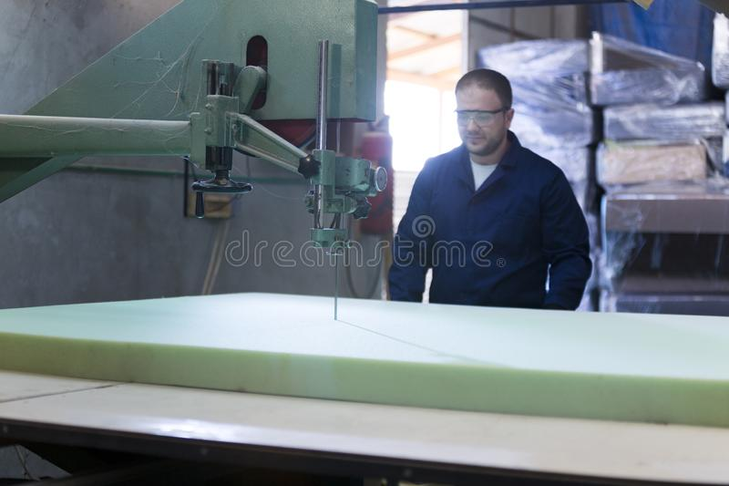 Il giovane in una fabbrica della mobilia sta tagliando la schiuma per il sofà fotografie stock libere da diritti