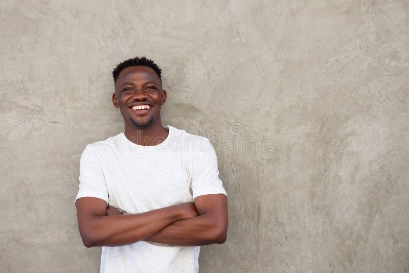 Il giovane uomo africano bello che sorride con le armi ha attraversato dalla parete fotografia stock