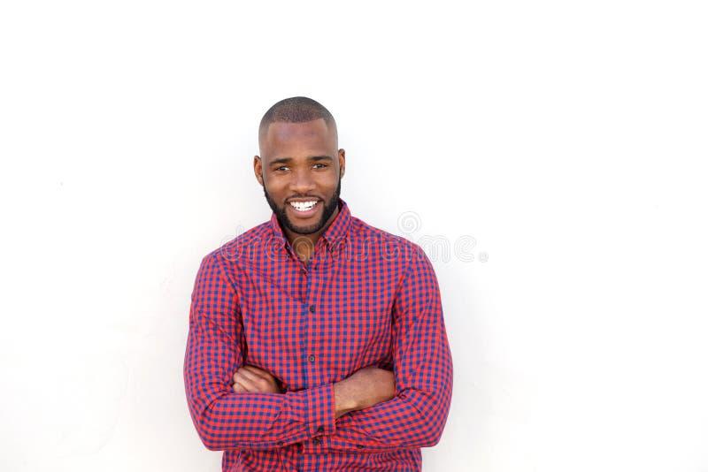 Il giovane uomo africano bello che sorride con le armi ha attraversato dalla parete bianca fotografia stock