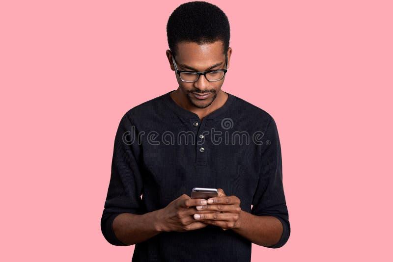 Il giovane uomo africano bello tiene lo Smart Phone, scarica gli archivi L'uomo pelato scuro veste l'attrezzatura casuale nera, u fotografie stock libere da diritti